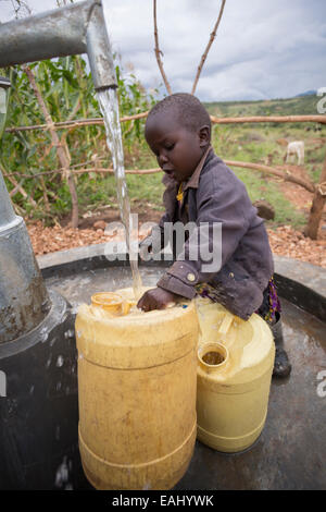 Three year-old Abigail Chemtai is the first to draw water from a newly installed well in Sukuroi village, Bukwo - Stock Photo