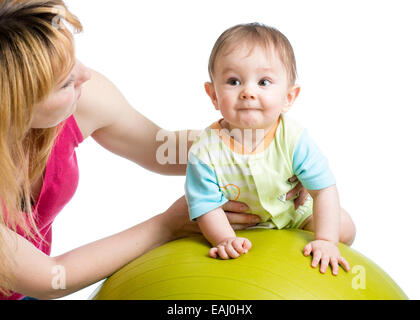 mother doing gymnastics with baby on fit ball - Stock Photo
