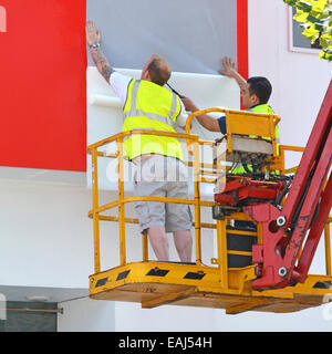 Cherry picker access platform in use by workmen fixing sheets of graphics forming a big advert display on side of - Stock Photo