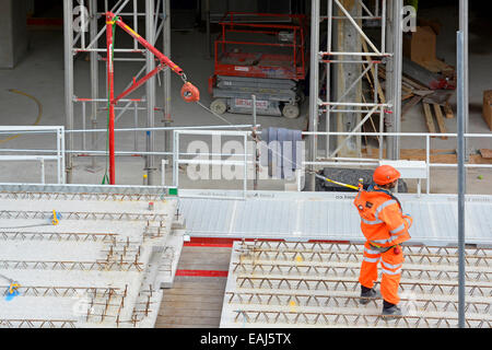 Fall prevention restraint system in use by workman on raised platform with safety harness worn under high visibility - Stock Photo