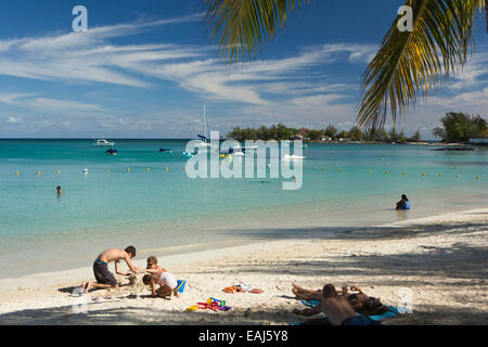 Mauritius, Pereybere, public beach, visitors relaxing on sand in sunshine - Stock Photo