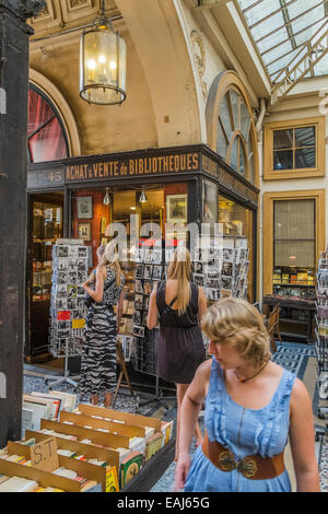 people in front of an antiquarian bookstore in the  historic indoor shopping mall galerie vivienne, paris - Stock Photo