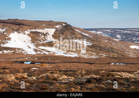 Late winter snowdrifts on the slopes of Kinder Scout in the Peak District, Derbyshire. Evening sunlight. - Stock Photo