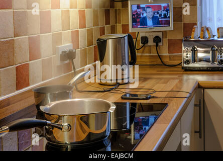Many appliances being used in a modern kitchen.Heavy electrical consumption. - Stock Photo