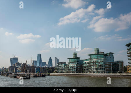 View from a boat of modern riverside apartments at Wapping on the north bank of the River Thames with the city behind. - Stock Photo
