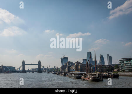 House boats and barges moored at Wapping on the north bank of the River Thames with the City of London and Tower - Stock Photo