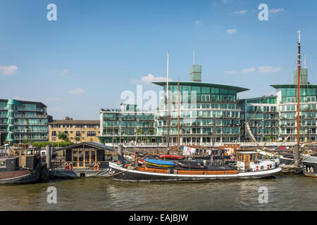 House boats and barges moored at Wapping on the north bank of the River Thames with modern apartment buildings behind. - Stock Photo