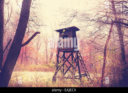 Vintage filtered photo of hunting pulpit in forest. - Stock Photo