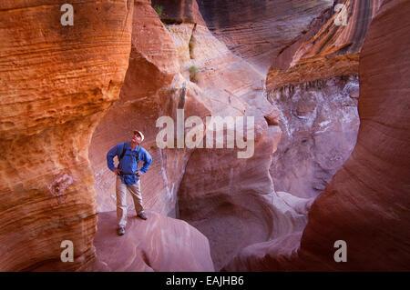 A hiker explores a slot canyon in Canyonlands National Park near Moab, Utah. - Stock Photo