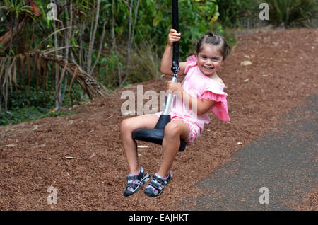 Child girl (age 04) rids on Flying Fox play equipment in a children's playground. - Stock Photo