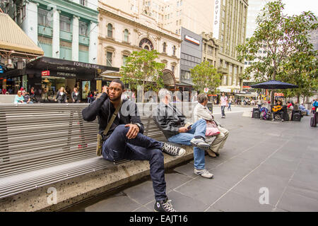 People sitting on benches in Bourke Street Melbourne - Stock Photo