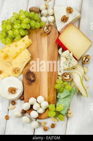 various types of cheese with fruits and nuts on a wooden table - Stock Photo
