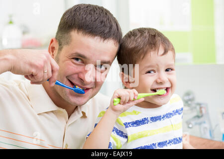 father and child brushing teeth in bathroom - Stock Photo