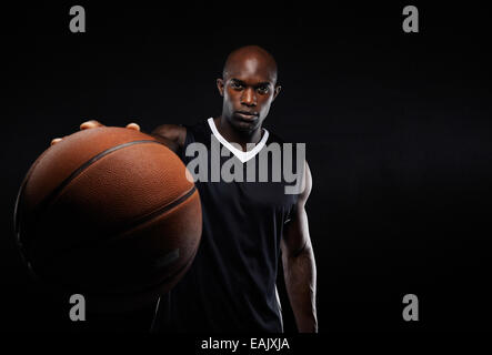 Image of young African American man in sports jersey holding a basketball. Professional basketball player against black. Stock Photo