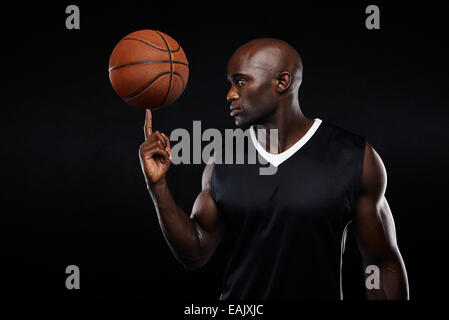 Portrait of young African athlete balancing basketball on his finger against black background. Focused basketball - Stock Photo