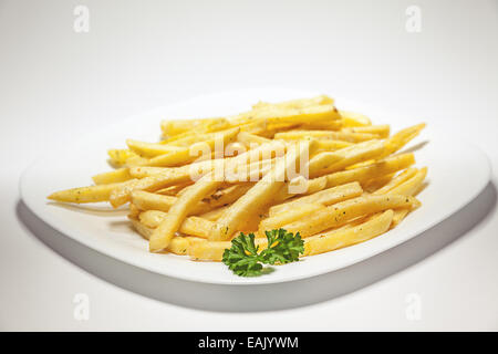 French Fries served on white plate, decorated with a branch of parsley. - Stock Photo