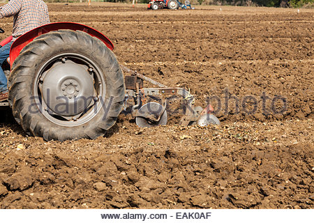 Tractor ploughing field - close up - Stock Photo