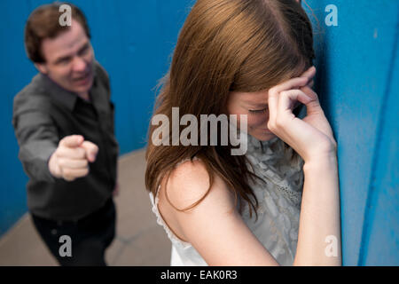 Tearful young woman in the foreground, with aggressive man, lower down in shot behind her. - Stock Photo