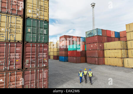 Businessmen and worker walking near cargo containers - Stock Photo