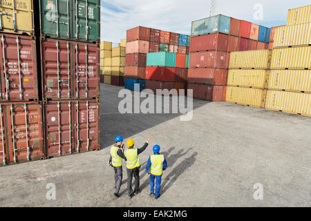 Businessmen and worker talking near cargo containers - Stock Photo