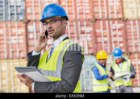 Businessman talking on cell phone near cargo containers - Stock Photo
