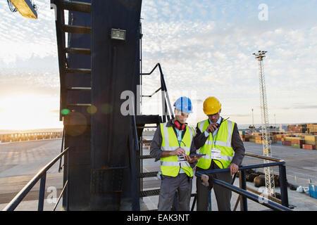Workers using walkie-talkie on cargo crane - Stock Photo