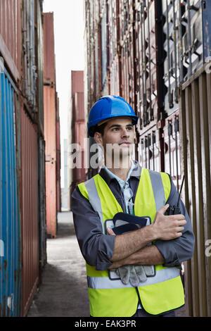 Worker standing between cargo containers - Stock Photo