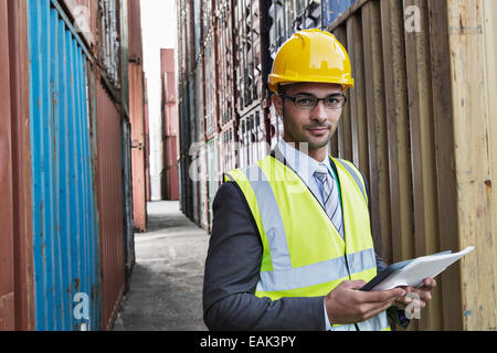 Businessman holding digital tablet between cargo containers - Stock Photo