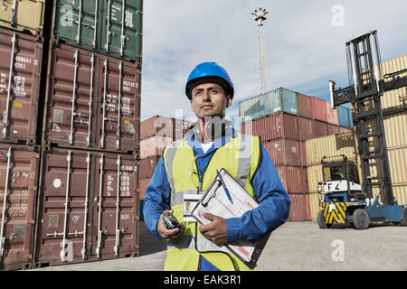 Worker holding clipboard near cargo containers - Stock Photo