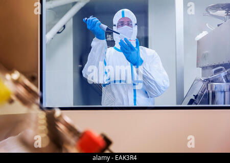 Scientist in clean suit pipetting sample into Petri dish in laboratory - Stock Photo