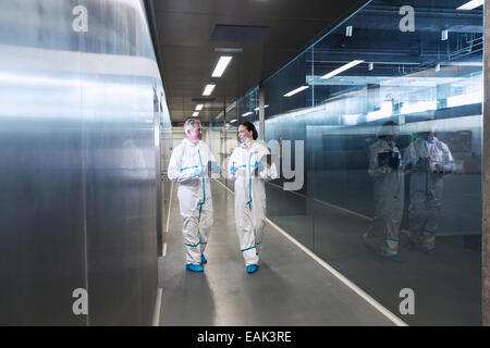 Scientists in clean suits walking in hallway - Stock Photo