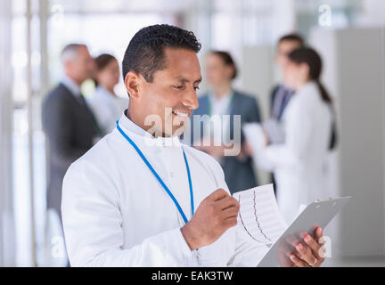 Scientist reading clipboard in hallway - Stock Photo