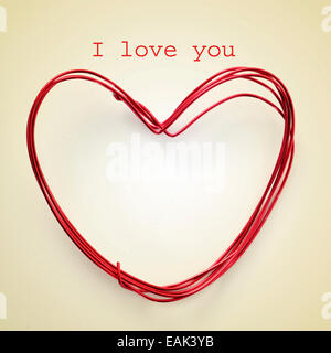 sentence I love you and a heart-shaped roll of wire on a beige background, with a retro effect - Stock Photo