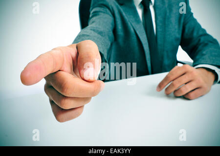 man wearing a suit sitting in a table pointing with the finger the way out - Stock Photo