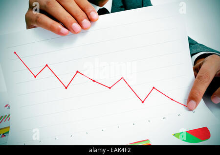 man wearing a suit sitting in a table showing a graph of economic losses - Stock Photo