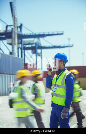 Worker using walkie-talkie near cargo containers - Stock Photo