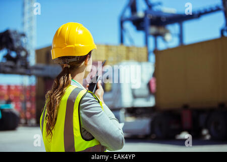 Businesswoman using walkie-talkie near cargo containers - Stock Photo