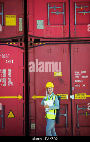 Businesswoman talking on cell phone near cargo containers - Stock Photo