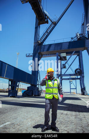 Worker talking on cell phone near cargo crane - Stock Photo