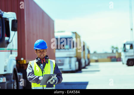 Worker using digital tablet near trucks with cargo containers - Stock Photo