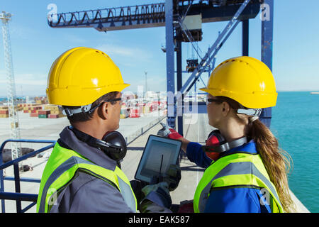 Workers using digital tablet on cargo crane - Stock Photo