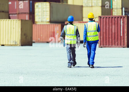 Workers walking near cargo containers - Stock Photo