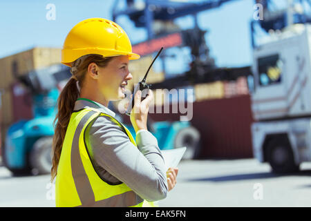 Businesswoman using walkie-talkie near cargo containers and trucks - Stock Photo