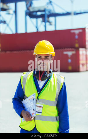 Worker carrying clipboard near cargo containers - Stock Photo