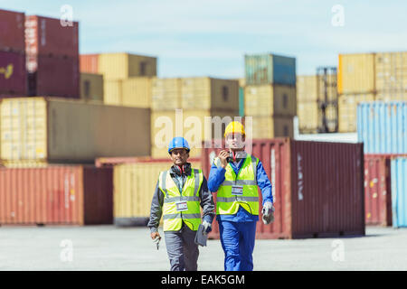 Worker and businessman walking near cargo containers - Stock Photo