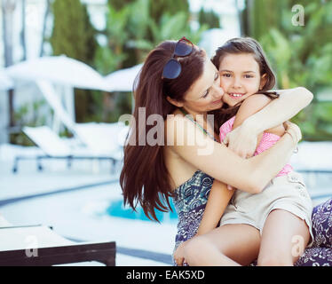 Mother embracing her daughter on poolside - Stock Photo