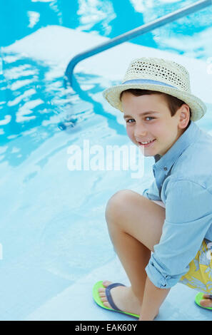 Portrait of smiling boy wearing straw hat crouching by swimming pool - Stock Photo