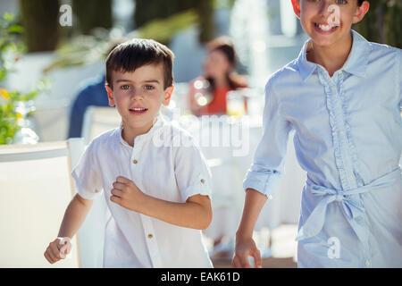 Smiling boy and girl running towards camera outdoors - Stock Photo