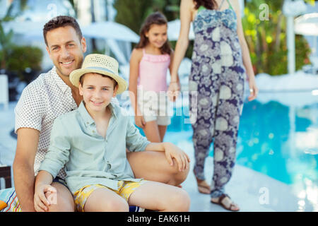 Family enjoying themselves by swimming pool - Stock Photo