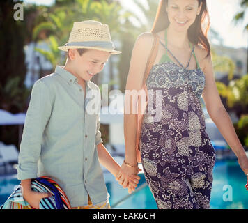 Mother and son holding hands by swimming pool - Stock Photo